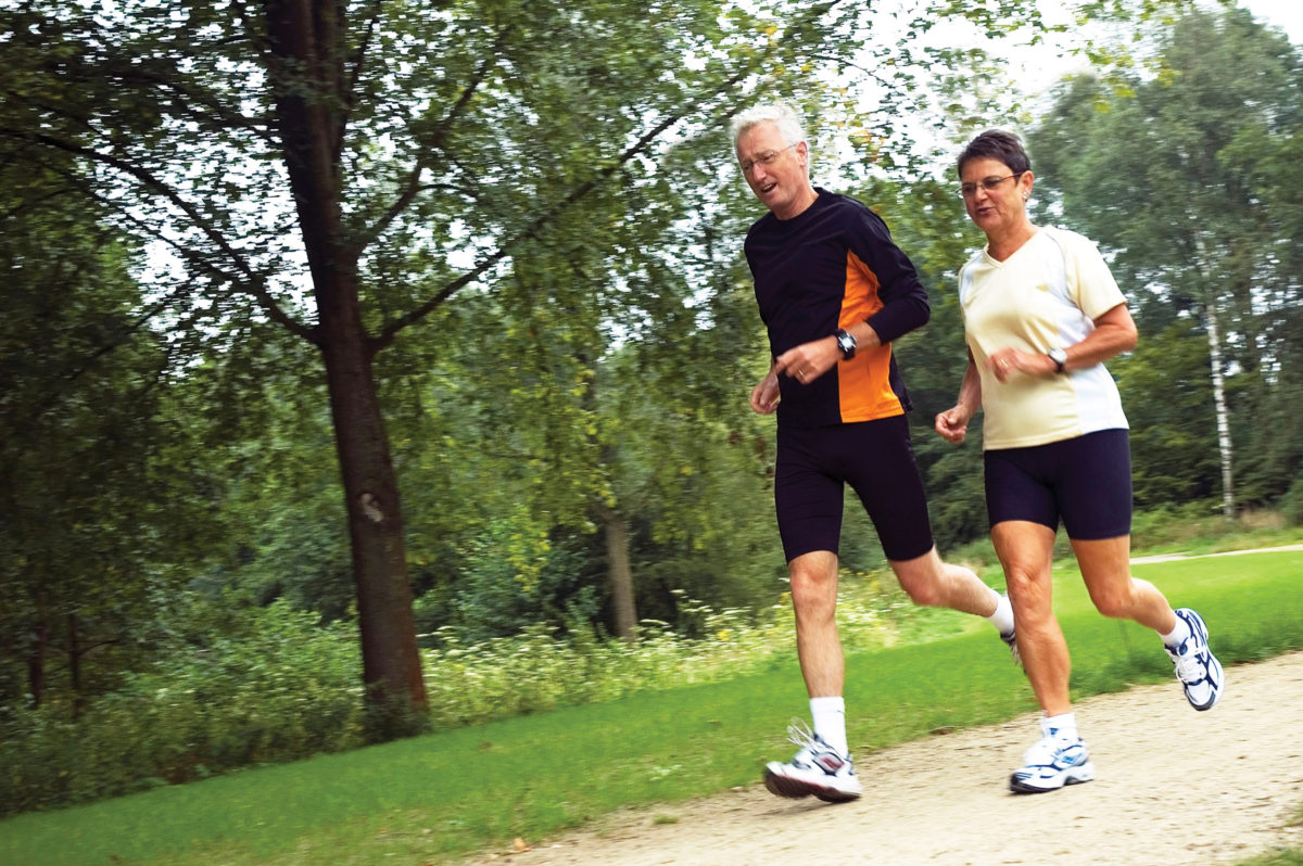 Healthy couple running in park.