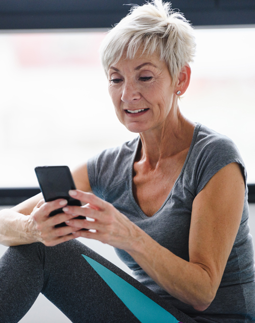 Excited woman scheduling her next online training session with OneUp.