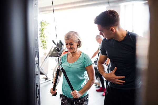 older woman with trainer in the gym